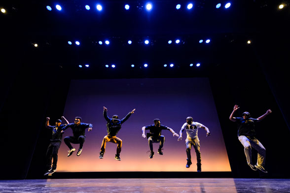 Dancers jumping mid-air on stage. Imaging the Self program.