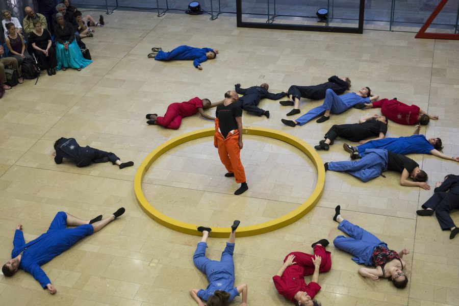 Students pose in a circle during a dance performance in the Chazen Museum of Art lobby