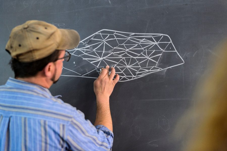 Peter Krsko draws a biological-based structure on a chalkboard while teaching a class, Zoethica: Bioinspired Art and Science