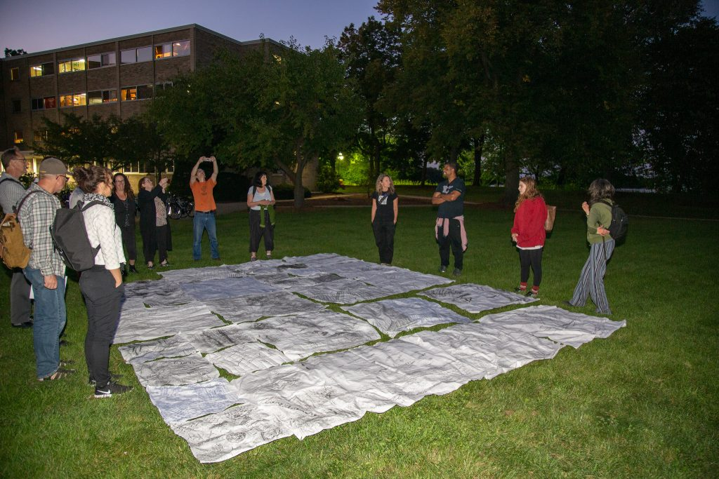 Participants surround charcoal rubbings laid out on grass.