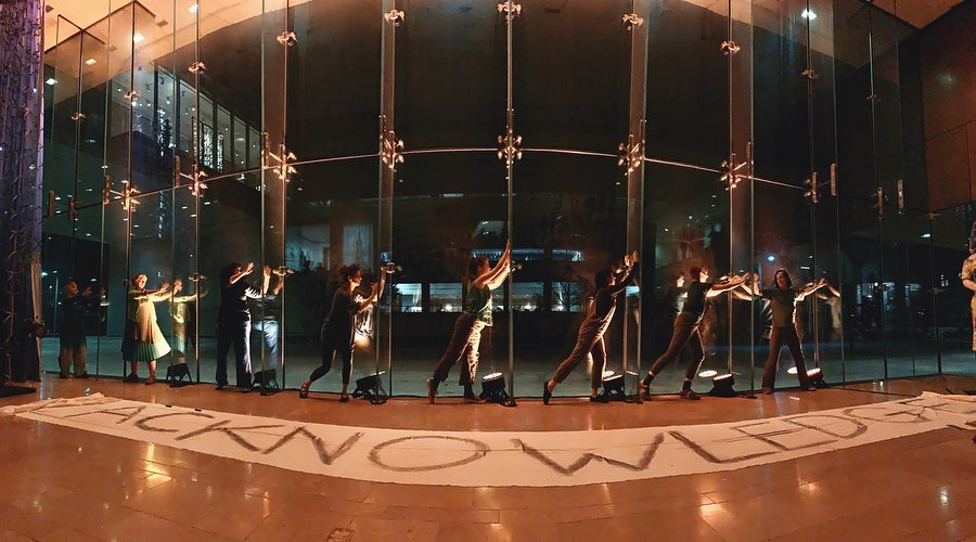 "Dancers pose in front of a glass window and a banner on the floor reads ""Acknowledge"""