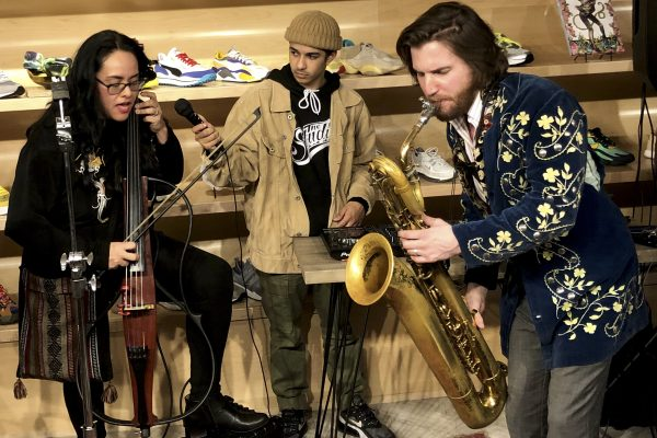 Musicians perform with an electric cello, a microphone, and a baritone saxophone.