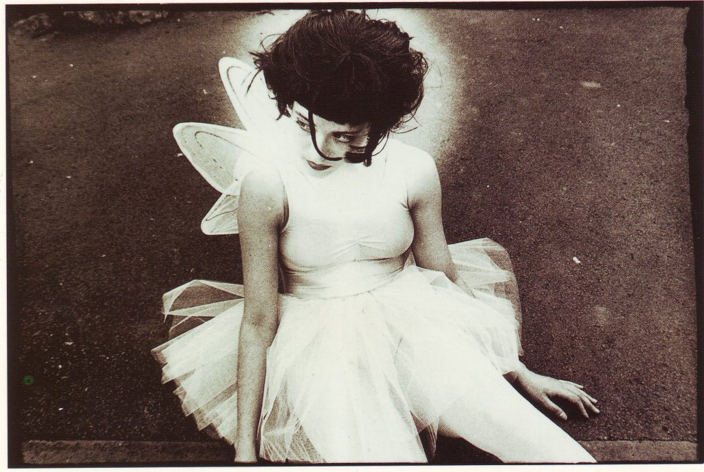 Litza Bixler sitting in a white dress with wings