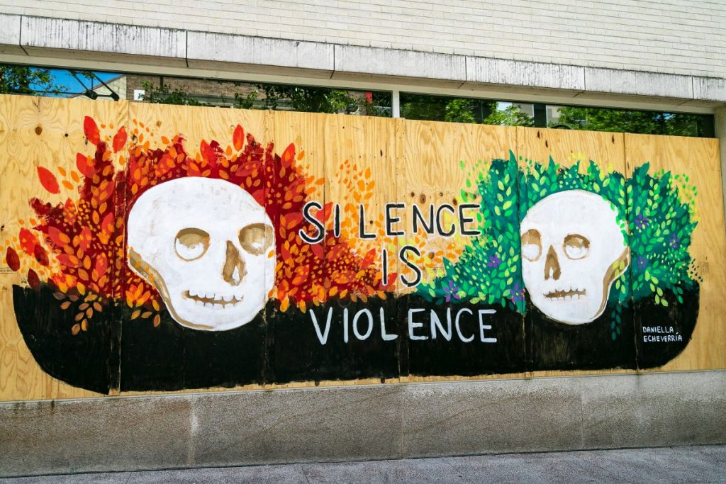 """Mural with two skulls at left and right, in front of a vibrant red/orange and green leaf motif, with the words """"Silence is Violence"""" in between the two skulls."""