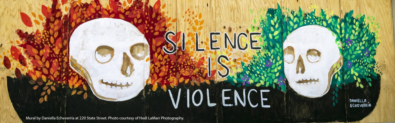 "Mural with two skulls at left and right, in front of a vibrant red/orange and green leaf motif, with the words ""Silence is Violence"" in between the two skulls."