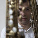 Arun Luthra headshot behind a saxophone