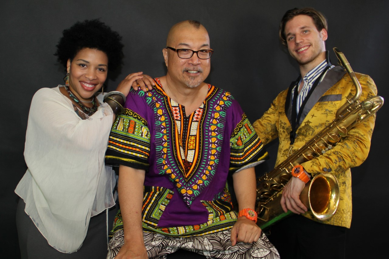 Musicians Iyanna Jones (left), Fred Ho (middle), and Ben Barson (right) holding a baritone saxophone. Photography by Ana Pereno.