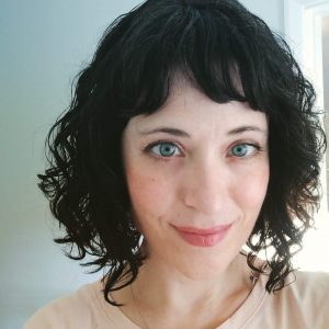 photo of a pale skinned woman with dark hair and blue eyes